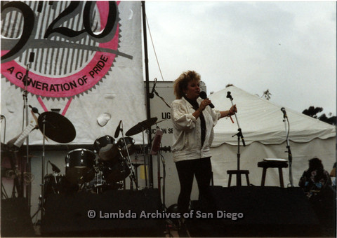 P024.395m.r.t 1989 San Diego Pride: Sue Fink in the white jacket performing on stage with band