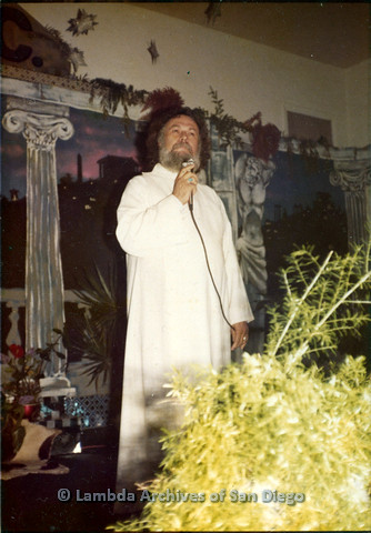 P110.019m.r.t Metropolitan Community Church: Joseph Gilbert wearing white robe with microphone in front of colonnade backdrop.