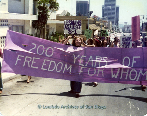 "P109.007m.r.t San Diego Pride Parade 1976: ""Lesbians against Senate Bill S-1"" marching behind banner that says ""200 Years of Freedom For Whom""."