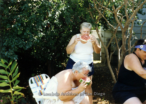 P024.328m.r.t Commonwealth: Ila Suzanne (center, seated) and Sally Hopkins (center, standing) eat watermelon.