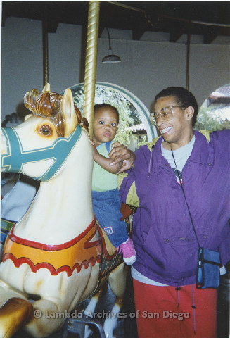 P125.002m.r.t Marti Mackey smiling widely at Phyllis Jackson's grandchild riding the carousel