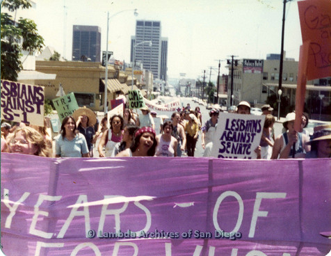 "P109.008m.r.t San Diego Pride Parade 1976:  ""Lesbians against Senate Bill S-1"" marching behind banner that says ""200 Years of Freedom For Whom""."