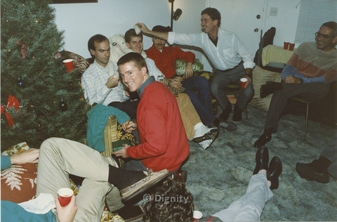 P104.089m.r.t Dignity San Diego: man in red holding gifts under a Christmas tree while a group of men play in the background
