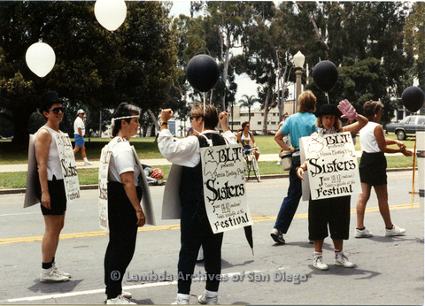P024.413m.r.tSan Diego Parade in Balboa Park:(L to R) Kithy Gately, Judy Bennett, unidentified and Ellie Rapp (Beautiful Lesbian Thespians).marching in parade wearing signs.