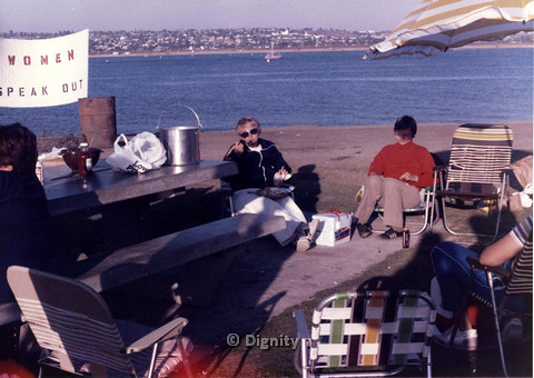 "P104.024m.r.t Dignity San Diego: Women eating near the beach with sign ""WOMEN SPEAK OUT"" in background"