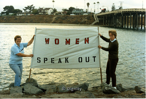 "P104.018m.r.t Dignity San Diego: Lucy(?) and woman by the ocean, holding a sign that read ""WOMEN SPEAK OUT"""