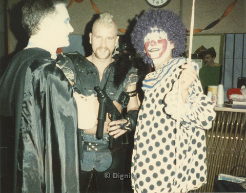 P104.103m.r.t Dignity San Diego: A punk and clown posing for camera, while a vampire looks to the right