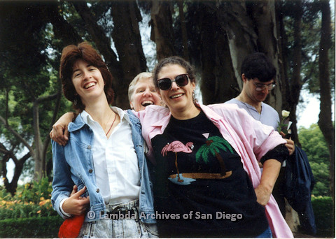 P024.502m.r.t 1989 San Diego Pride: (Left to right) Marghi Kilmer with arm around unknown woman and Sally Hopkins peeking up from behind
