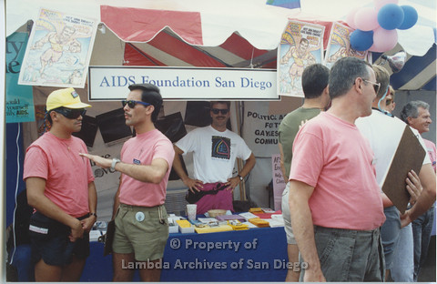 P001.058m.r Pride 1991: People standing in front of the AIDS Foundation of San Diego booth (Peter Cooper is the second person from the left)