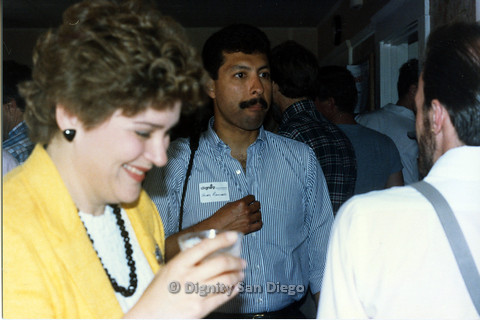 P103.188m.r.t Dignity San Diego: Candid shot of a woman in yellow laughing with Henry Ramirez in center