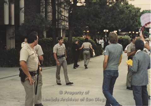 P024.086m.r.t Myth California Protest, San Diego, June 1986:Diane F. Germain being escorted away by a police officer