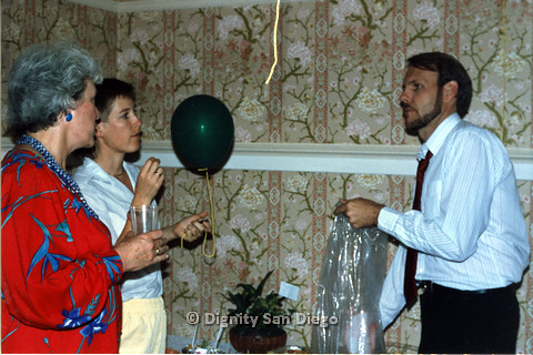 P103.192m.r.t Dignity San Diego: Bruce Neveu looking at two people holding a cup and a balloon