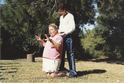 P001.206m.r.t Retreat 1991: man in blue stripped pants with his hands on the shoulder of a man kneeling in a pink t-shirt
