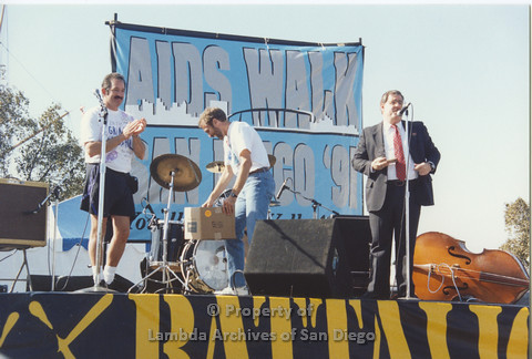 P001.127m.r.t AIDS Walk 1991: 3 people on stage, man in suit speaking