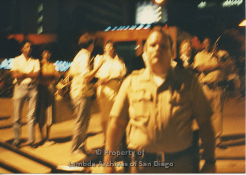 P024.137m.r.t Myth California Protest, San Diego, June 1986: blurry photo of people standing behind a police officer