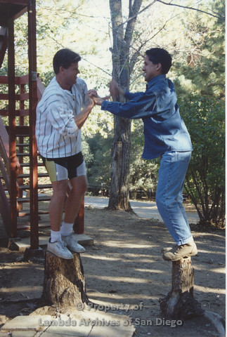 P001.203m.r.t Retreat 1991: 2 men standing on tree stumps playing a game