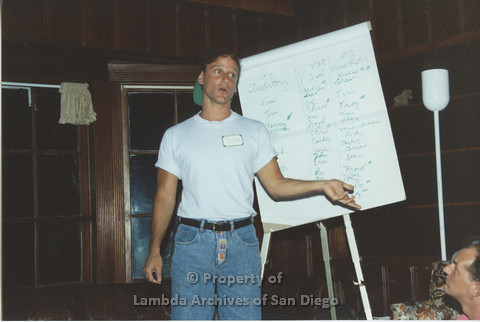 P001.214m.r.t Retreat 1991: man in front of an easel pad wearing a nametag (Andrew)