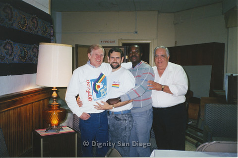 P103.134m.r.t Dignity San Diego:  Four men posing for camera next to lamp, Stan Lewis at center right