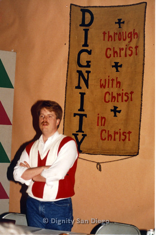 P103.095m.r.t Dignity San Diego:  Man in white and red shirt standing in front of Dignity sign