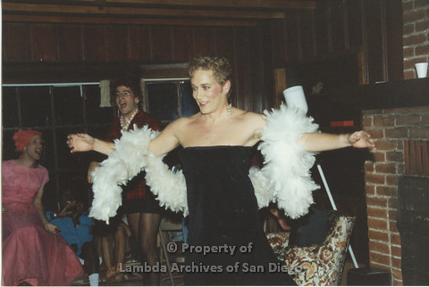 P001.218m.r.t Retreat 1991: man in drag wearing a black dress and a white boa