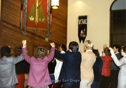 P103.047m.r.t Dignity San Diego: Church congregation standing with hands clasped together and held in the air