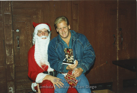 P001.270m.r.t X-mas: blonde man in jean jacket sitting on Santa's lap