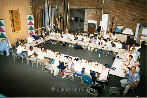 P103.093m.r.t Dignity San Diego: Large group of people sitting around a long table waving at camera