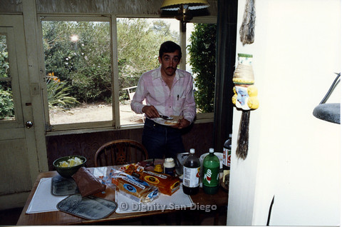 P103.078m.r.t Dignity San Diego: Man in pink plaid standing in front of food