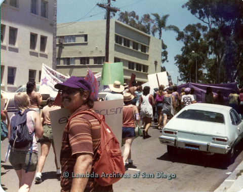 P109.006m.r.t San Diego Pride Parade 1976: Man wearing purple hat and backpack looking over shoulder in midst of march.