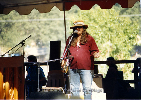 P024.271m.r.t Woman in red jacket standing on day stage talking in to microphone.
