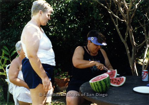 P024.321m.r.t Commonwealth: Sally Hopkins (standing, left) looks on as a woman cuts a watermelon in to slices.
