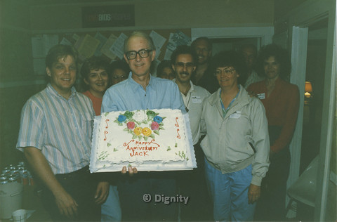 P104.084m.r.t Dignity San Diego: Jack Shuck holding anniversary cake while Bruce Neveu (black shirt in back), John M., Michelle (both tagged in beige), and other people surround him