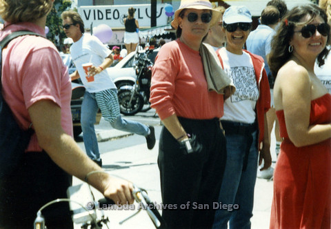 P024.479m.r.t 1990 San Diego Pride Parade: Group of people, woman in salmon shirt in center