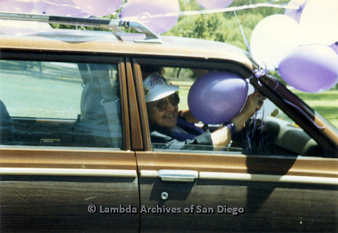 P024.524m.r.t 1990 San Diego Pride: Muriel Fisher rides in the passenger side  of a car holding balloons out the window