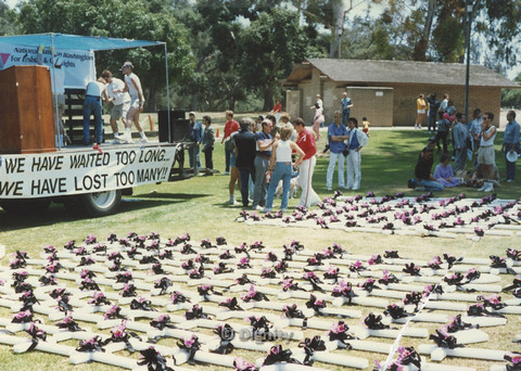 "P104.144m.r.t San Diego Pride Festival: Crosses laid out over field as memorial to gay and lesbian dead with a wagon in background bearing text ""WE HAVE WAITED TOO LONG… WE HAVE LOST TOO MANY!!"""