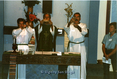 P103.012m.r.t Dignity San Diego: Male church leader and altar people, Earl on right, holding communion