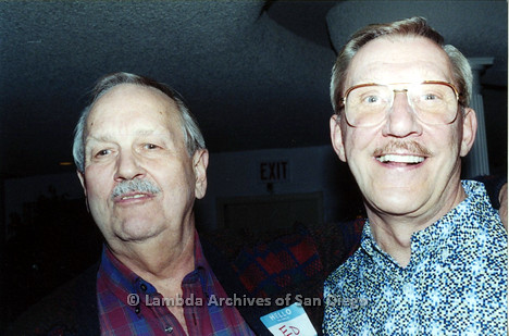 P040.034m.r.t SAGE General Meeting; 2 men, one on left with nametag (ED), one on right with glasses.