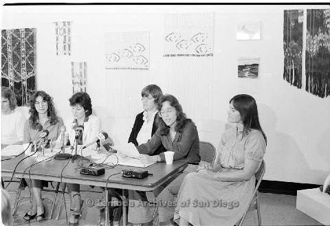 P123.019m.r.t Dixon Press Conference 1982:  (Left to Right) Chris Russell, Kathy Gilberd (MLTF, NLG), Diane Cooper (NOW/SD), Susan McGreivy (ACLU), Kim McAlister (CWSS), Eileen Bingle sitting while Kim speaks