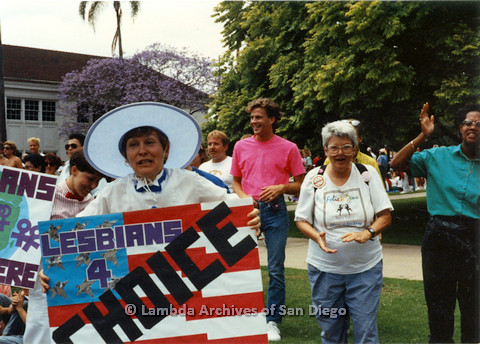 "P024.513m.r.t 1990 San Diego Pride: Diane Germain (on left) holding a sign that reads, ""Lesbians 4 choice"" and Cinthia Rich (on right)"
