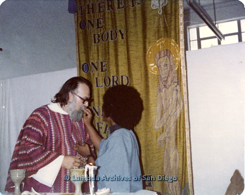 P110.053m.r.t Metropolitan Community Church: Joseph Gilbert receiving communion from religious leader.