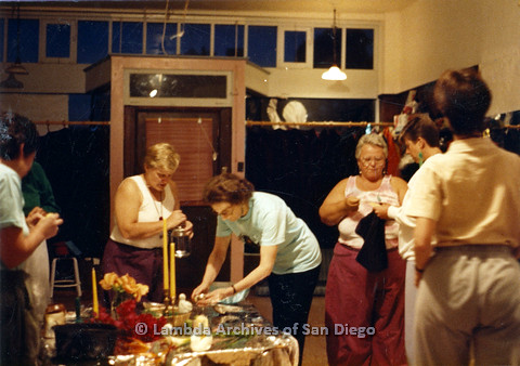 P024.306m.r.t Sally Hopkins in white tank-top (left), Ila Suzanne in magenta pants holding a black fabric (center right), and Karen Belcher in a white sweater (right) stand around a table