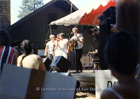 P024.224m.r.t A line of women performs on Day stage while audience looks on.