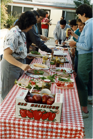 P104.172m.r.t Dignity San Diego: A group of people clustered around a table preparing plates of food.