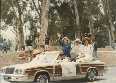 "P104.138m.r.t San Diego Pride Festival: Group of four people in a wood paneled car with ""Mr Miss Gay Pride"" poster on side."