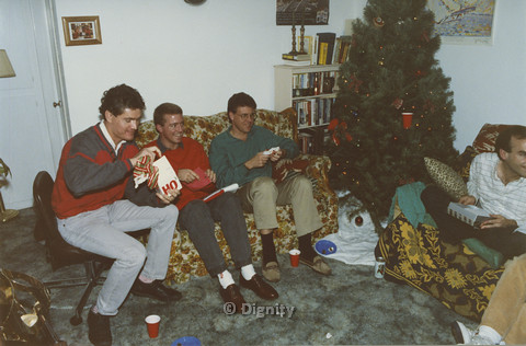 P104.091m.r.t Dignity San Diego: Four men sitting while opening Christmas presents