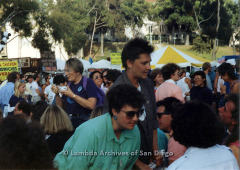 P024.456m.r.t 1990 San Diego Pride festival: Crowd, woman in turquoise in foreground.