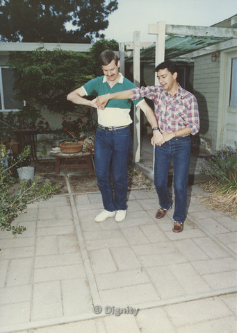 P104.111m.r.t Dignity San Diego: Rick Duffer (right) holding hands with another man on a patio dancing.