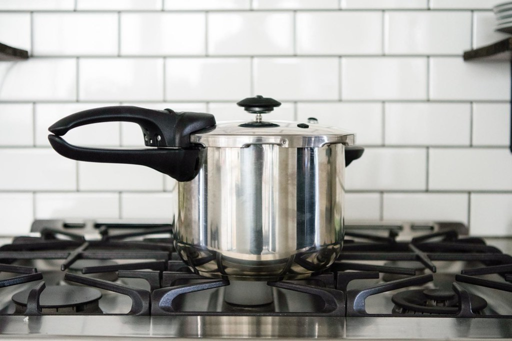 Pressure cooker on stovetop in kitchen with lid sealed after cooking releasing pressure