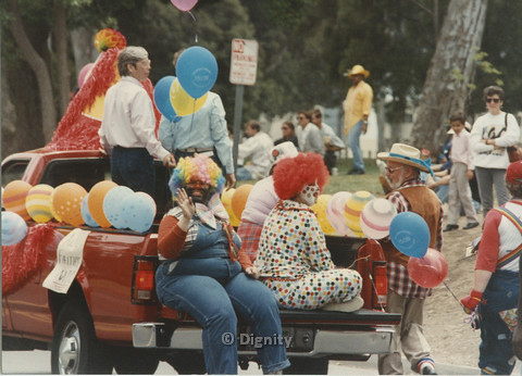 P104.125m.r.t San Diego Pride Parade: Group of people wearing clown outfits in bed of red truck.