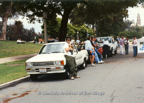 P024.465m.r.t 1990 San Diego Pride Parade: Virginia Cunningham leans against white truck.